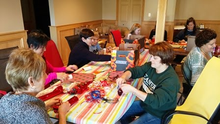 photo of volunteers stuffing treat rolls with candy and wrapping them in tissue paper